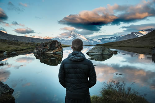 A person in a winter coat looks over a placid mountain lake