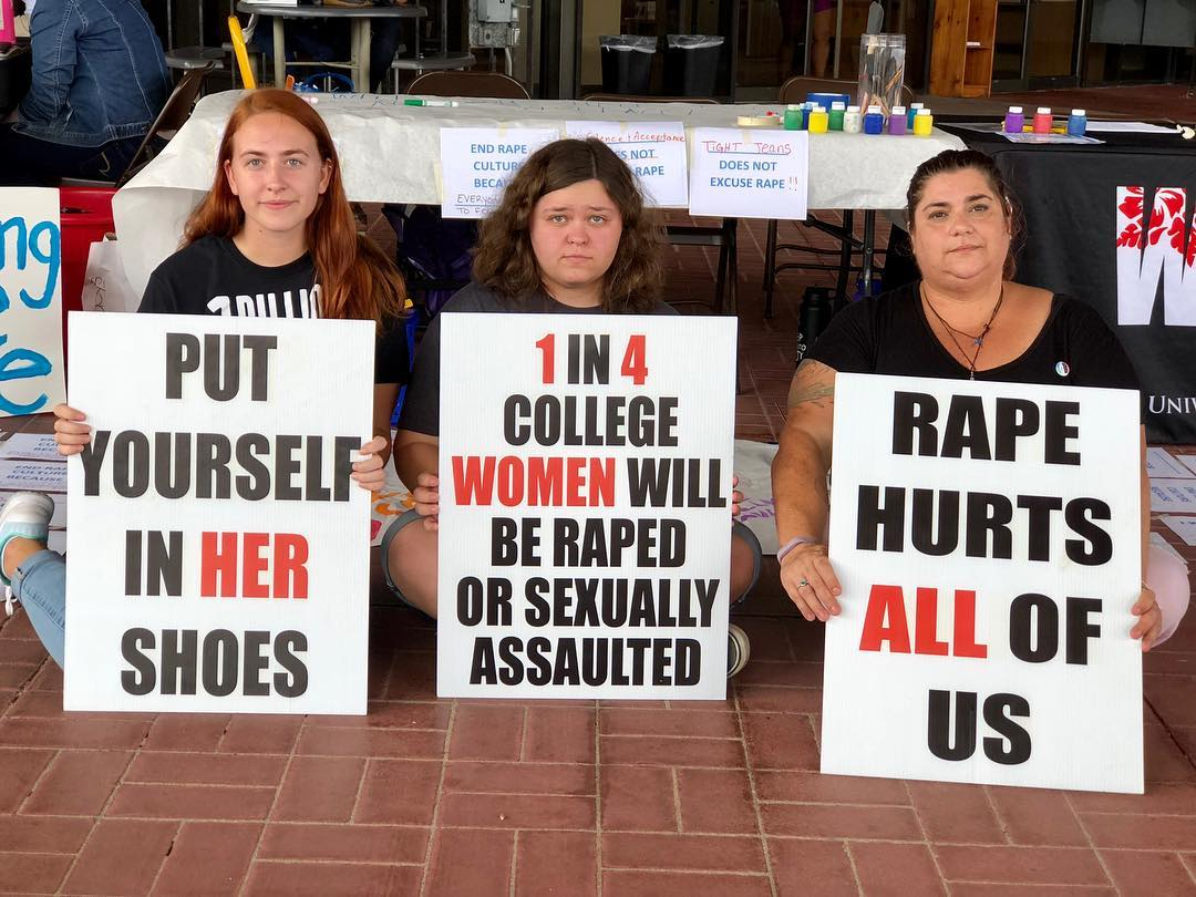 Women holding signs at a women's center tabling event - The signs read 'Put Yourself in HER shoes', '1 in 4 college WOMEN will be raped or sexually assaulted' and 'Rape Hurts ALL of us'