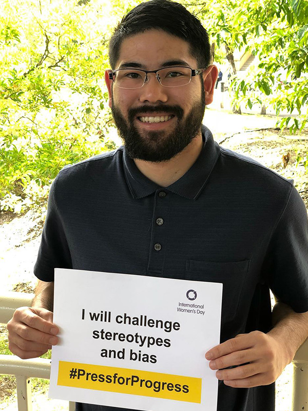 Young man holding a sign for International Women's Day 2018: 'I will challenge stereotypes and bias