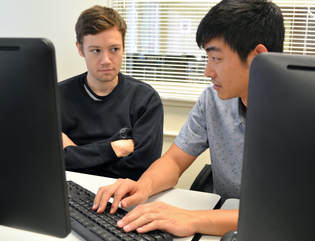 Students discuss a programming problem at a computer lab